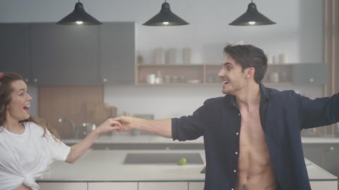 Excited couple having fun at domestic kitchen. Attractive man holding woman hand Live Action