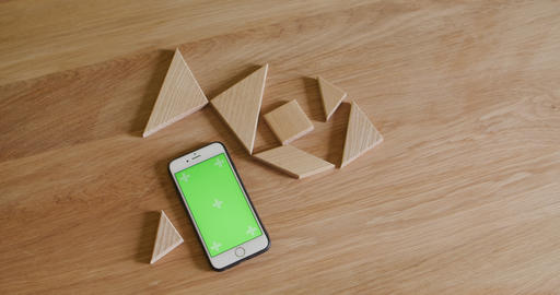 Smart phone on wooden table wood with wooden tangram Live Action