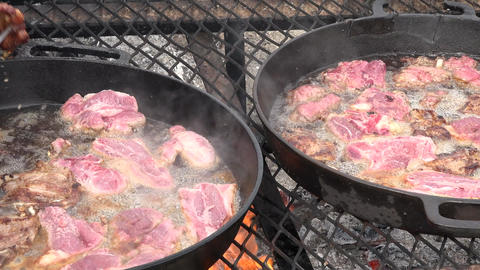 Cooking mutton chops meat cast iron pan over camp fire 4K 019 Footage