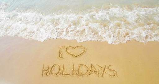 golden sand with beach and tropical sea wave movement, write text on sand i love holiday with heart Live Action