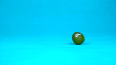 Lime with eyes in a woman hand close-up. Lime shakes and twists eyes on a blue Live Action