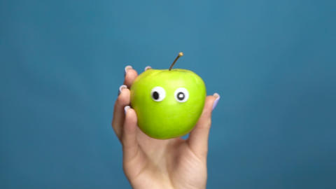 Green apple with eyes in a woman hand close-up. Apple shakes and twists eyes on Live Action