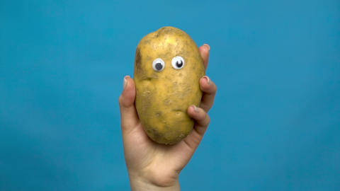 Potato with eyes in a woman hand close-up. Potatoes shakes and twists eyes on a Live Action