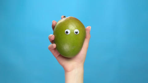 Mango with eyes in a woman hand close-up. Mango shakes and twists eyes on a blue Live Action
