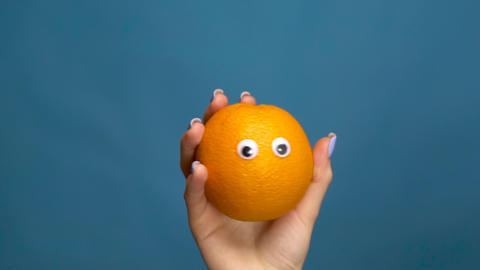 Orange with eyes in a woman hand close-up. Orange shakes and twists eyes on a Live Action