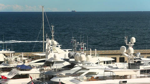 View of motor boat is on horizon through masts of yachts, luxury life Live Action