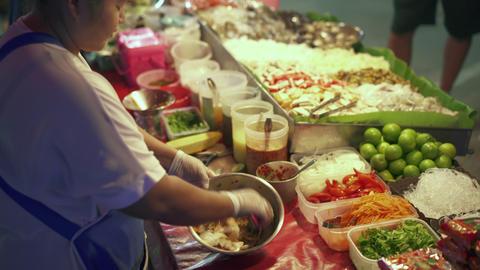 Street food vender making som tom papaya salad in food market in Thailand Live Action
