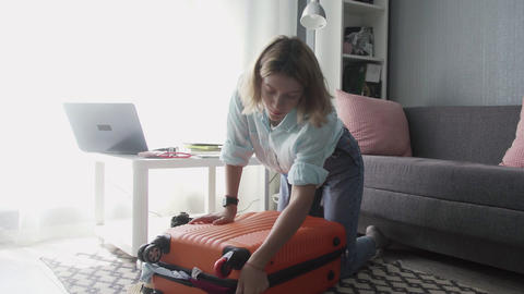 Travel woman packing suitcase getting ready for road trip, preparing luggage for Live Action