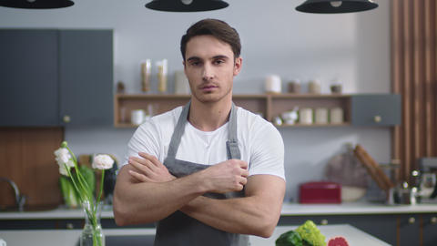Smiling chef man looking camera at home kitchen. Handsome man crossing hands Live Action
