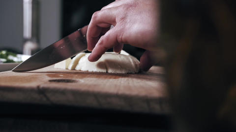 Close up of chef cutting the parmesan cheese on the cutting board Live Action