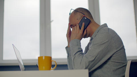 Depressed adult businessman talking by mobile phone front laptop in office Live Action