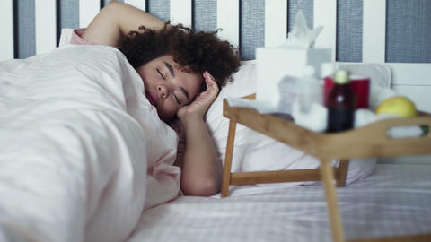Ill young african american girl is sleeping during disease lying in bed Live Action