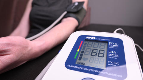 people checks blood pressure. The device shows the patient's blood pressure Live Action