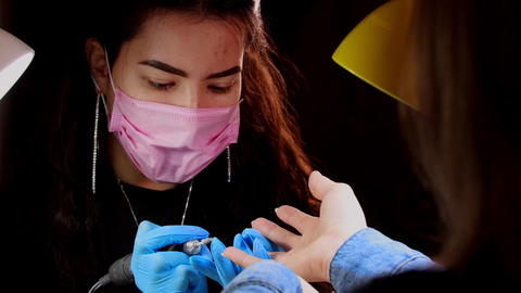 Master doing manicure using hardware instrument with cone nozzle Live Action