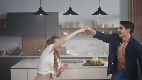 Young couple dancing together at home kitchen. Happy friends having fun indoors Live Action