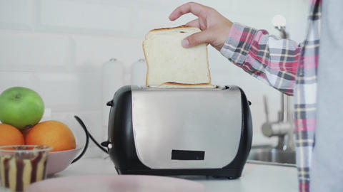 A man puts bread in a toaster. The bread is fried. Breakfast food is being Live Action