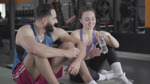 Young Middle Eastern man flirting with slim Caucasian woman in gym. Bearded Live Action