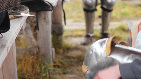 Man putting on armour plates before knights tournament at outdoor history museum Footage