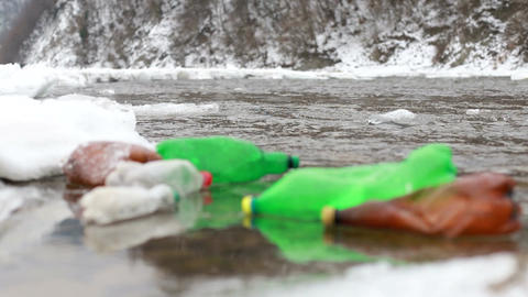 Environmental pollution. Plastic bottles, bags, trash in river, lake. Rubbish Live Action