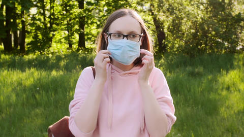 Young trendy girl wearing protective medical mask outdoors in the park Live Action