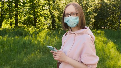 Portrait of a young trendy girl in a medical protective mask with a smartphone Live Action
