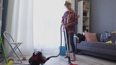 Woman use vacuum cleaner to cleaning the floor in living room during daily clean Live Action