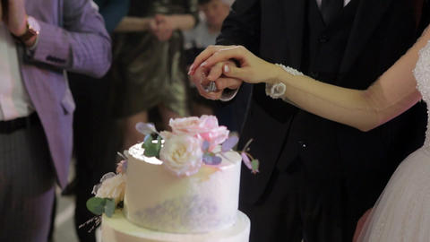 Brides cut wedding cake. A bride and a groom is cutting their wedding cake. Hands of bride and groom Live Action