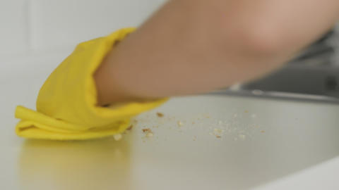 Housewife woman in yellow gloves clean crumbs on the table with yellow rag Live Action