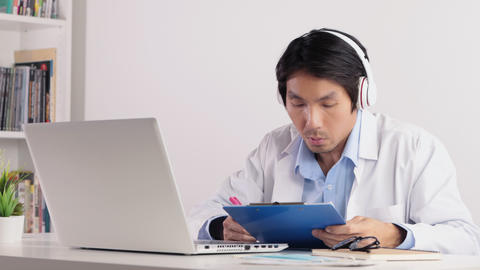 Asian Male Doctor Write Report and Meeting Pass Video Conference by Laptop Live Action