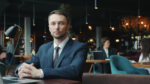 Portrait of attractive young businessman looking at camera with serious face at Live Action