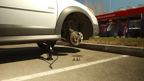 Woman rolls car wheel and places the front wheel in place Live Action