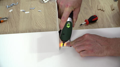 Male hands using electric screwdriver GIF