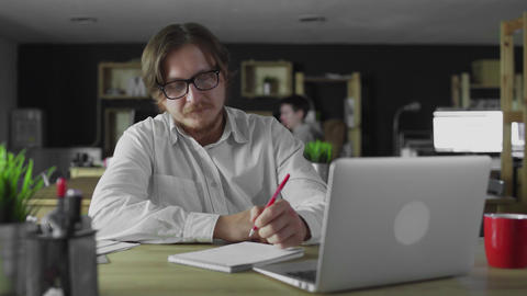Young manager is working in office writing sitting at desk alone Live Action