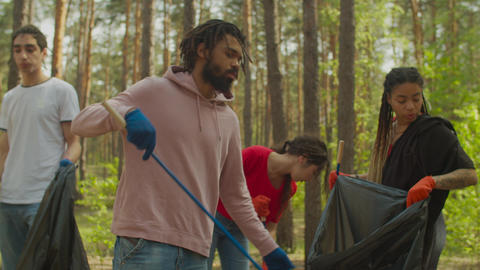 Eco-friendly people cleaning woodland from trash Live Action