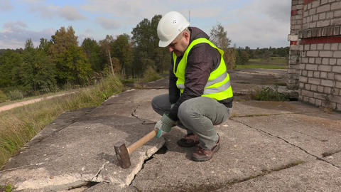 Worker with sledgehammer beats concrete Footage