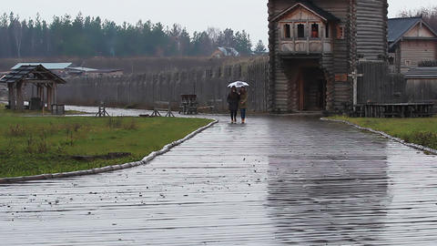 Best friends walking in the rain in the architectural complex. Rainy autumn Footage
