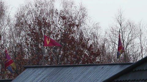 Vintage flags with blazons swaying in the wind on a wooden house roof, autumn Footage