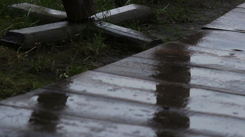 Raindrops falling on wooden pathway in abandoned amusement park, autumn weather Footage