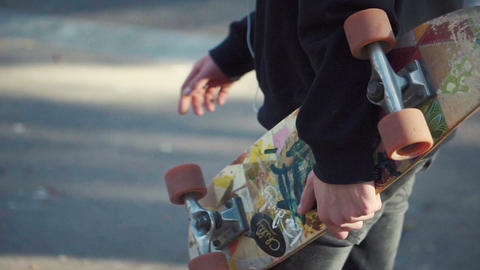 Young man walking and holding a skateboard in hand Footage