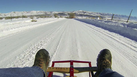 Man sled riding down winter ice snow rural road HD 001 Footage