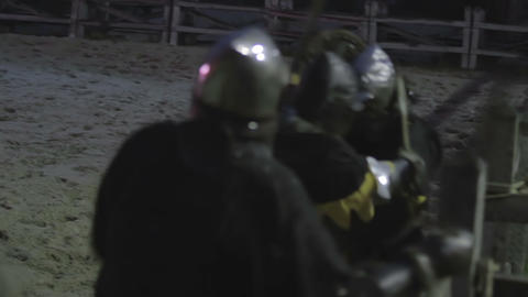 Fierce fight of three knights in heavy steel armor. Medieval battle reenactment Live Action