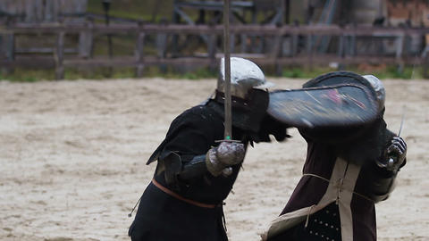 Medieval warriors sword fighting near the wooden fortress. Reenactment of battle Footage
