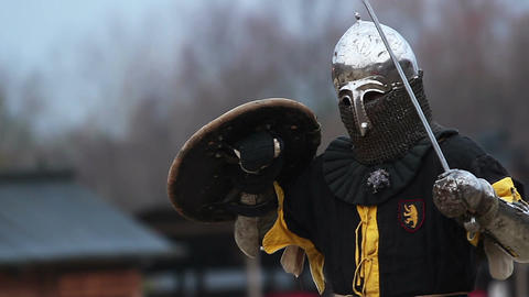 Mighty knight in steel armor getting ready for a fight, slow motion. Reenactment Footage