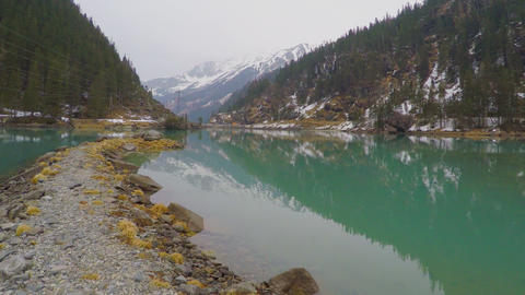 Stony lakeside, forest and mountains reflection in water, electric power lines Footage