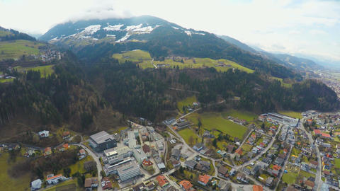Aerial shot of big city, beautiful Alps around it, green downhills, snowy peaks Footage