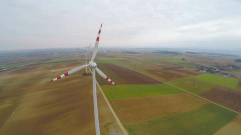 Wind turbines rotating on green field. Alternative source of energy. Aerial view Footage