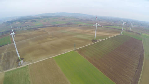 Wind turbines spinning on beautiful green fields, countryside. Renewable energy Footage