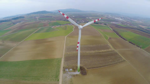 Rotating wind turbine on farmland. Alternative, renewable energy. Aerial view Footage