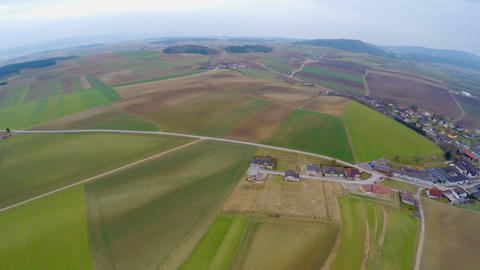 Helicopter view of green farmland and houses in countryside. Agricultural fields Footage