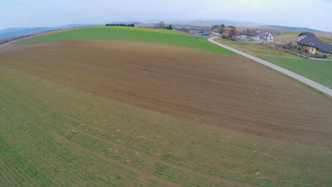 Flying across cultivated fields in countryside. Agricultural industry, farmlands Footage